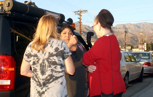Karen Perdue, left, who organized the Friday night vigil, talks with Lynda Greene and a friend of Greene's.