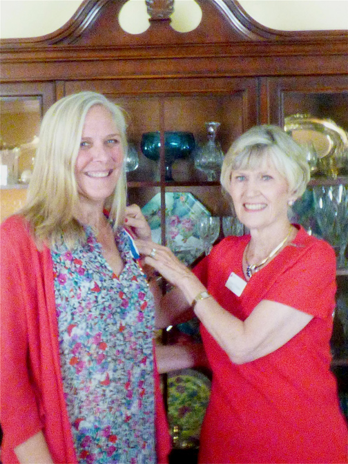 Outgoing DAR Chapter Regent Lynne Thompson, right, presents new Regent Caroline Craven with a DAR Regent's pin and ribbon.