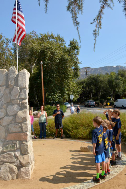 Photos by Dick CLUBB Boys from scout troop 302 and other community members salute the flag at the Crescenta Commons on Saturday morning.