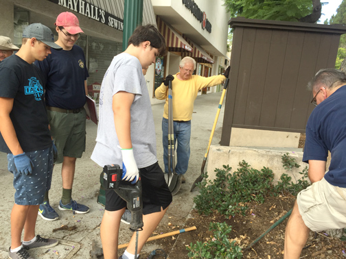 Januzik with his volunteers get direction on removing an old plaque from the grounds of the Montrose Shopping Park.