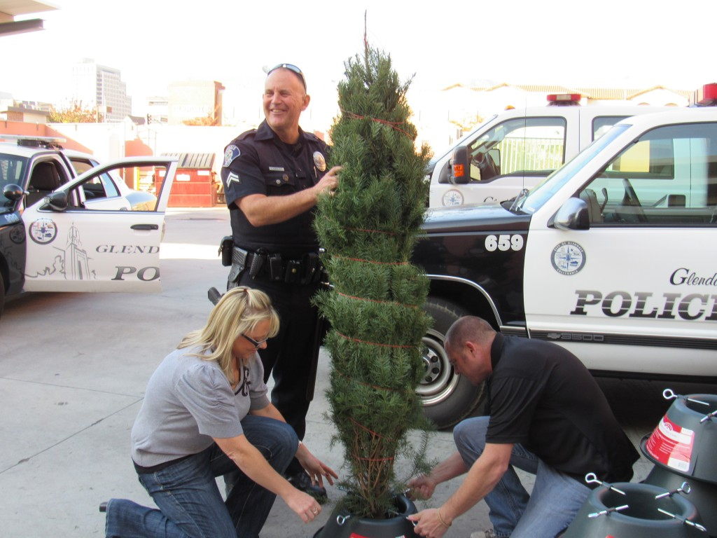 Amy-Tate, Agent Keith-Sobolsky and Sgt. Eric Webber prepare Christmas trees for delivery. Photo by Mary O'KEEFE