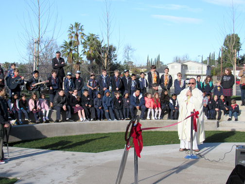 St. James' Father Ed Dover addressed the crowd prior to the ribbon cutting ceremony at the church campus on Tuesday morning.