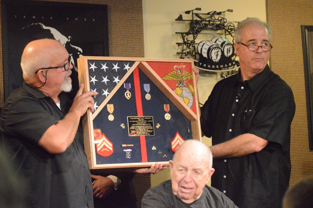 Jim Anderson (left) and Todd (right) hold up the shadow box of awards Anderson was given in addition to the Purple Heart.